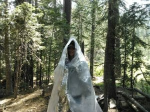 Women student uses modern material to provide her with protection from the rain. Survival - Emergency Shelter - Oregon