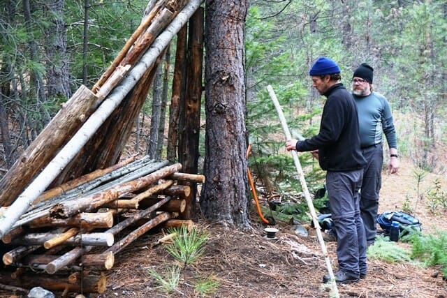 Staff and students building a lean-to shelter made of poles.