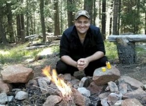 THE EDGE graduate Ryan by campfire smiling